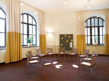 Heller inspirierender Seminarraum mit großen Fenstern und hohen Wänden